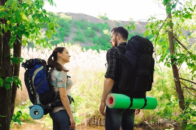 Concetto di avventura, di viaggio, di turismo, di aumento e della gente - coppia sorridente con gli zainhi all'aperto.