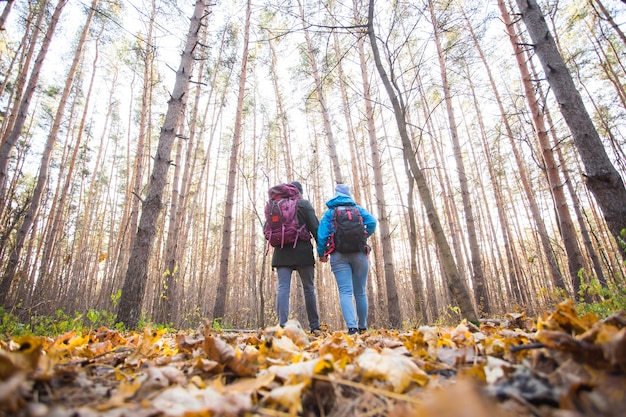 Concetto di avventura, viaggi, turismo, escursione e persone - giovane coppia con zaini nella foresta