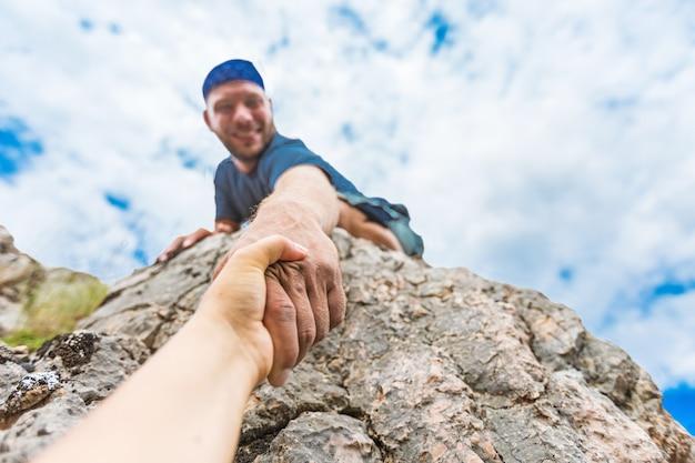 Avventurieri che si aiutano a vicenda per scalare la montagna