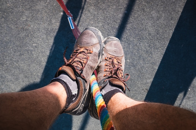 L'uomo avventuroso fa scivolare giù una corda, vista dai suoi stivali.