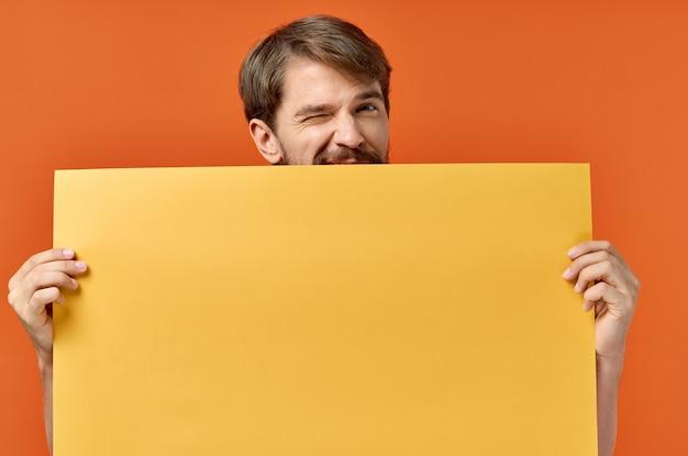 Cartello pubblicitario poster mockup uomo sullo sfondo arancione copia spazio. foto di alta qualità