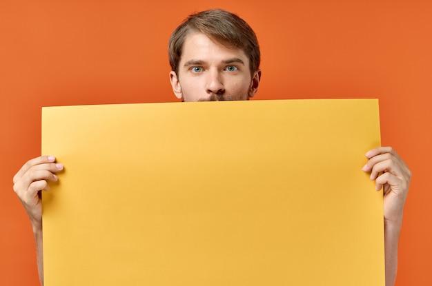 Cartello pubblicitario poster mockup uomo sullo sfondo arancione copia spazio.