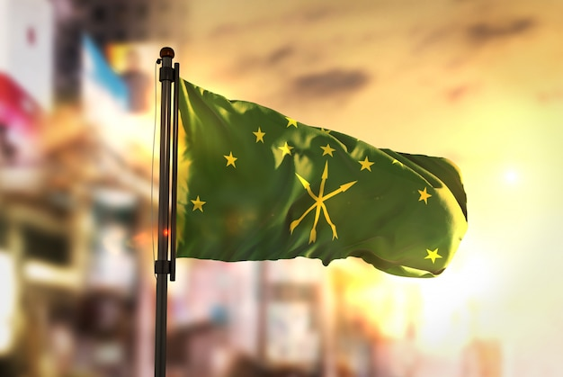 Bandiera adygea contro la città sfocata di sfondo al retroilluminazione di alba