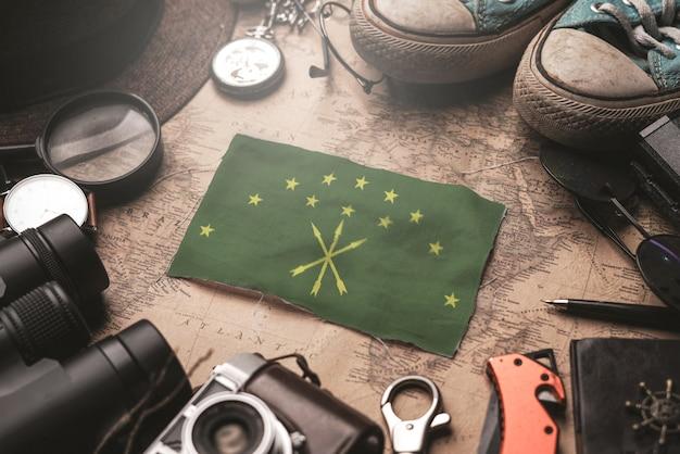 Bandiera di adygea tra gli accessori del viaggiatore sulla vecchia mappa vintage. concetto di destinazione turistica.