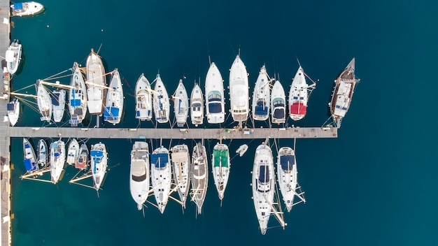 Porto sul mar egeo con più yacht ormeggiati vicino a moli, acqua blu, vista dal fuco, grecia