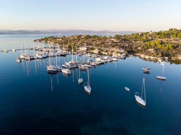 Porto sul mar egeo con più yacht ormeggiati vicino a moli, vegetazione, acqua blu, vista dal fuco, grecia
