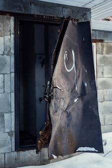 Edificio in blocchi di cemento cellulare con serratura rotta e telaio della porta danneggiato
