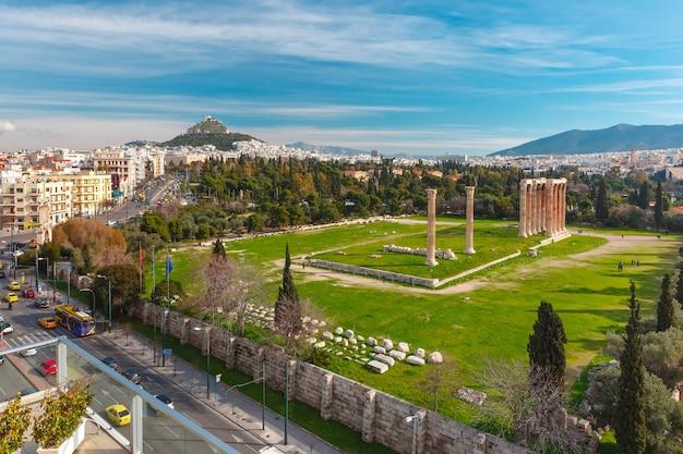 Vista aerea della città con rovine e colonne del tempio di zeus olimpio, monte licabetto in background, atene, grecia