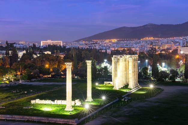 Vista aerea della città con rovine e colonne del tempio di zeus olimpio di notte, atene, grecia