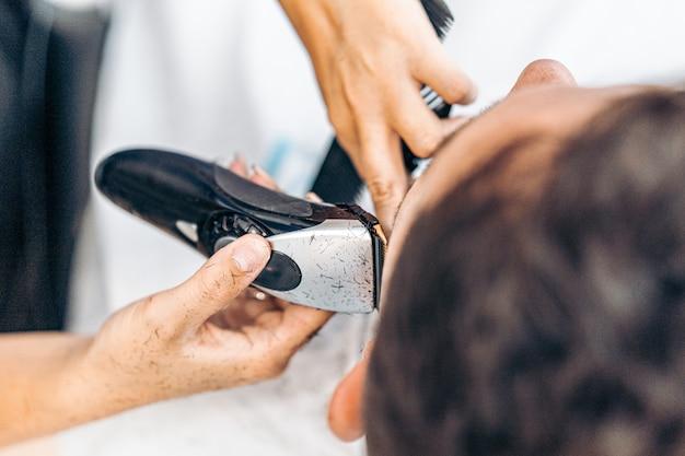 Vista ravvicinata aerea di un rasoio elettrico in metallo utilizzato per radere un cliente in un barbiere