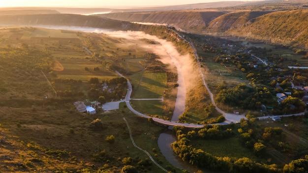 Vista panoramica aerea del drone della vecchia orhei al tramonto valle con fiume e villaggio di nebbia