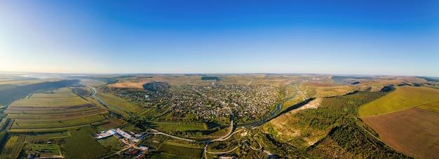 Vista panoramica del drone aereo di un villaggio in moldavia. valle con fiume, colline e campi in moldova