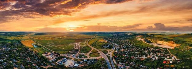 Vista panoramica del drone aereo di un villaggio e di una strada vicino a campi verdi