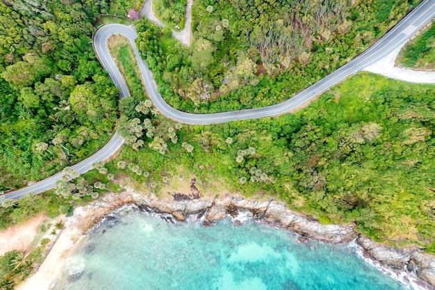 Drone aereo vista dall'alto verso il basso delle onde che si infrangono nella sabbia con strada e foresta