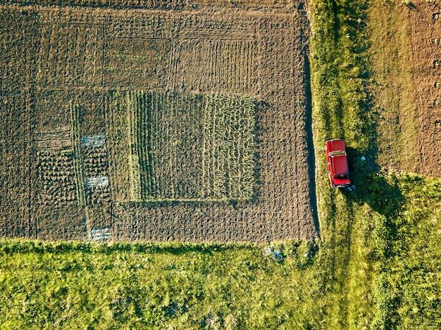 Vista aerea drone di auto su strada di campagna con campo di coltura agricola sui lati. l'auto è parcheggiata nel campo. rotto in macchina dopo un incidente nel campo su strada.