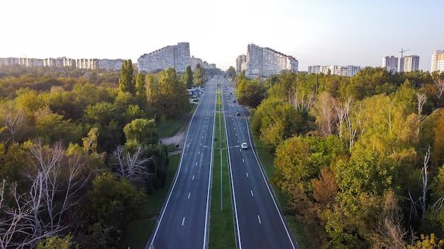 Vista aerea del drone di chisinau, moldova. strada con automobili e alberi lungo di essa che conduce alle porte della città di chisinau, edifici
