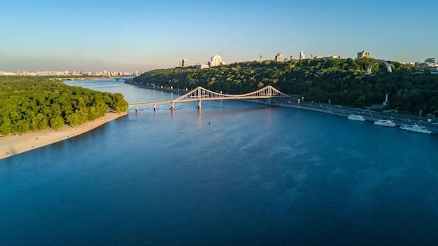 Vista aerea del fuco del ponte del parco pedonale, del fiume dnieper e del paesaggio urbano di kiev da sopra, città di kiev, ucraina