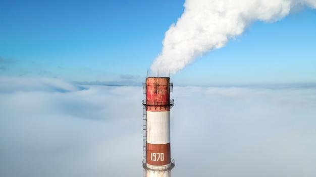 Vista aerea con drone del tubo della stazione termale visibile sopra le nuvole con fumo che esce. cielo azzurro e limpido