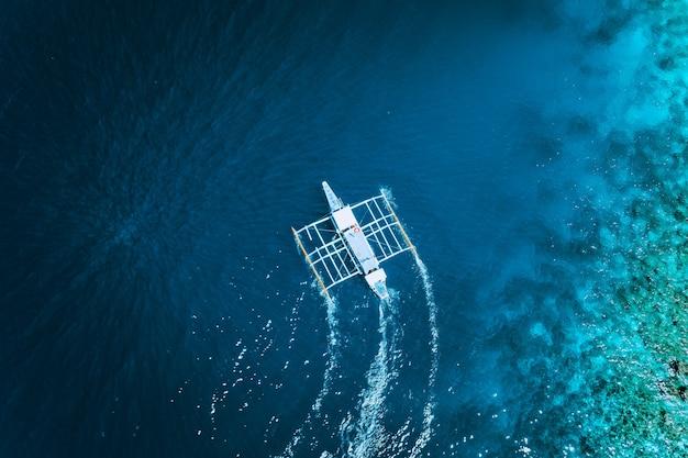 Vista aerea del drone della barca filippina tradizionale bianca che galleggia sulla superficie dell'acqua blu chiara. el nido, palawan, filippine.
