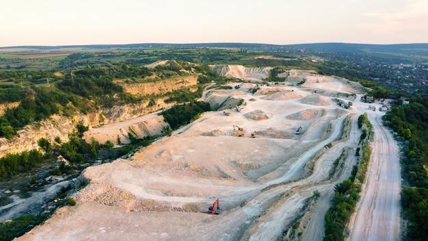 Vista aerea dei droni dei lavori in una cava di calcare in moldavia. campi e colline intorno, villaggio
