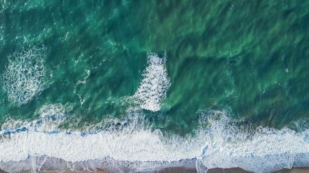 Aerea da drone di una splendida spiaggia di paesaggi marini con acqua turchese all'alba gratis