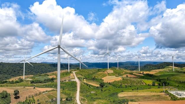 Vista frontale aerea del mulino a vento o del campo della turbina eolica sulla montagna e bella vista con cielo blu nuvoloso a khao kho, phetchabun, tailandia. luogo famoso per i turisti, energia pulita