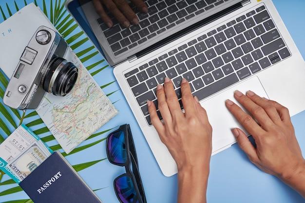 Aerea delle mani che pianificano il viaggio e il viaggio. accessori da viaggio piatti laici su superficie blu con fotocamera, mappa, laptop, passaporto, maschera facciale. vista dall'alto, concetto di vacanza.