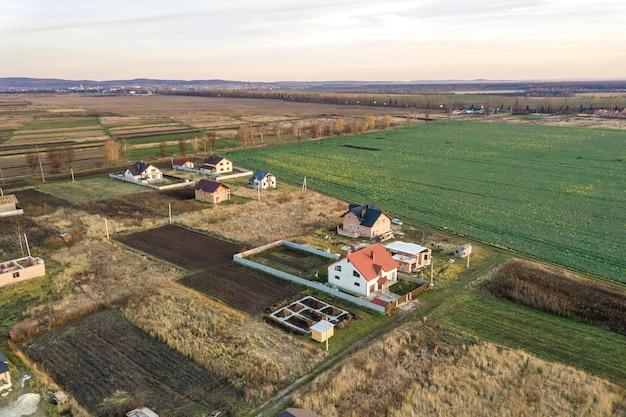 Paesaggio aereo di piccola città o villaggio con filari di case residenziali e alberi verdi
