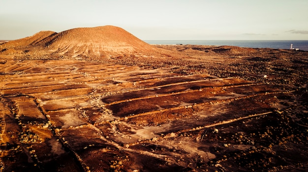 Paesaggio aereo con campo nel deserto terrestre e montagne con oceano