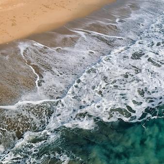 Colpo sopraelevato aereo delle onde del mare contro la riva del mare