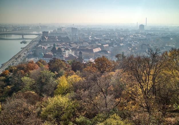 Paesaggio panoramico aereo sopra la parte storica di budapest con vista sul fiume danubio e alberi autunnali in prima linea.