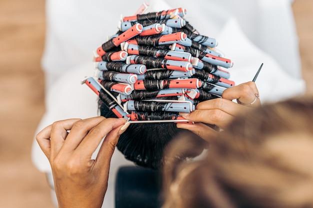 Foto aerea delle mani di un parrucchiere che fissa i capelli di un uomo con i bigodini in un salone