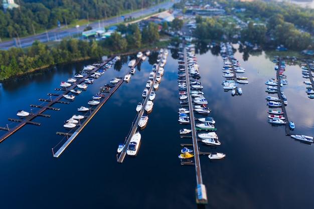 Ripresa aerea del molo della città con molte piccole barche in acqua blu con la riflessione e la prospettiva
