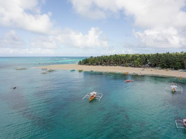 Ripresa aerea di una costa oceanica con spiaggia sabbiosa e alcune barche in acqua