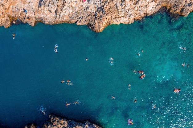Ripresa aerea di persone che nuotano nel mare adriatico circondato da scogliere sotto la luce del sole