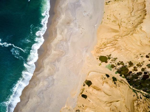 Ripresa aerea del mare e di una spiaggia sabbiosa