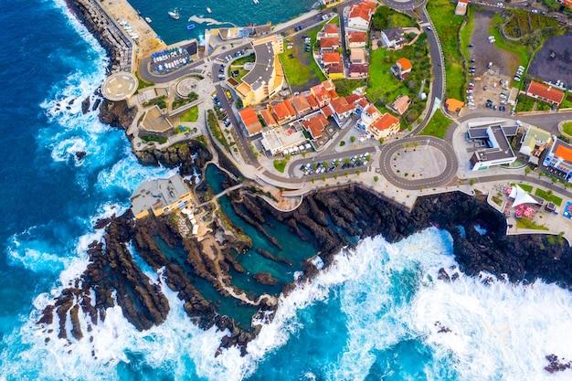 Ripresa aerea della città vicino al mare dell'isola di madeira con vista sull'oceano atlantico