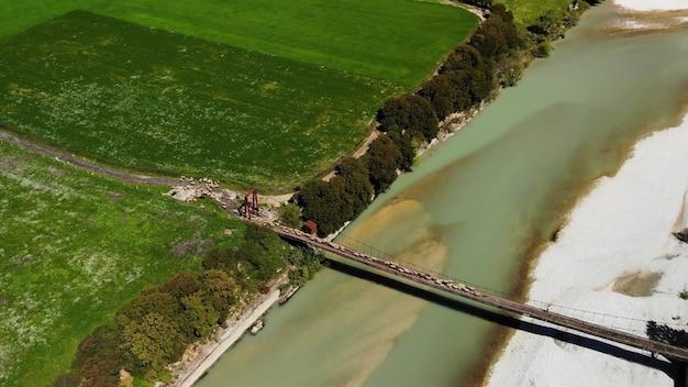 Vista aerea dall'alto verso il basso di pecore e montoni che attraversano il fiume montuoso sul ponte con pastore in