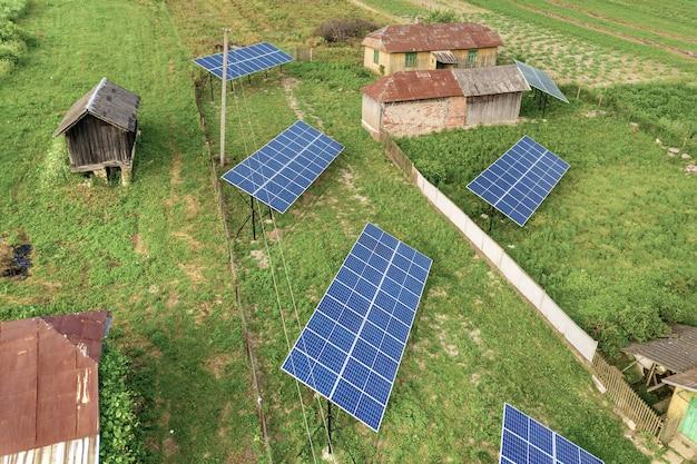 Vista aerea dall'alto in basso di pannelli solari in una zona rurale verde.