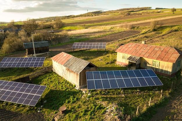 Vista aerea dall'alto verso il basso di pannelli solari nel cortile del villaggio rurale verde.