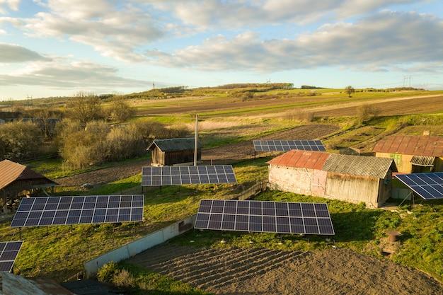 Vista aerea dall'alto in basso dei pannelli solari nel cortile del villaggio rurale verde.