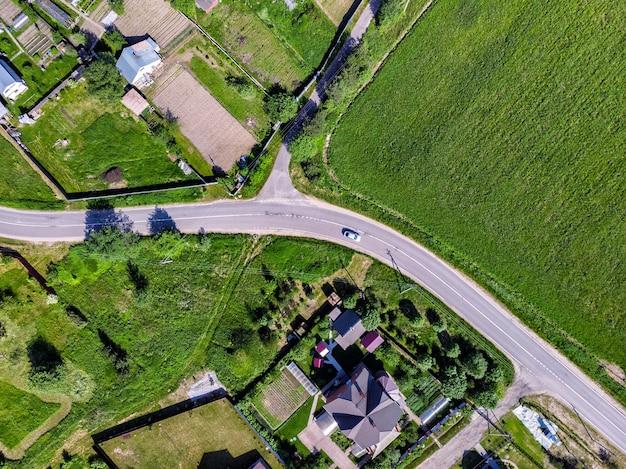 Vista aerea dall'alto drone della strada, delle case e dei campi