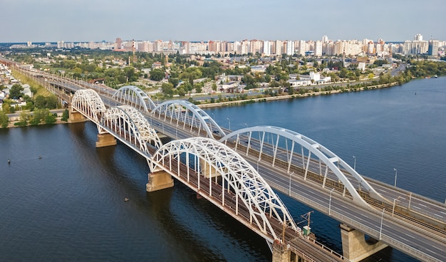 Vista aerea superiore del ponte darnitsky dell'automobile e della ferrovia attraverso il fiume dnepr dall'alto, kiev (kiev) skyline della città, ucraina