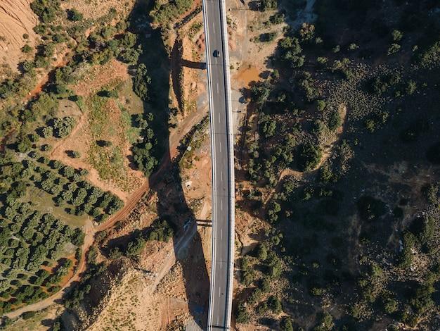 Vista aerea dall'alto da drone del paesaggio con strada asfaltata.