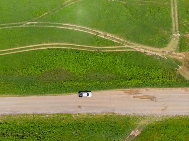 Vista aerea dall'alto strada sterrata tra i prati verdi con una piccola auto sulla strada