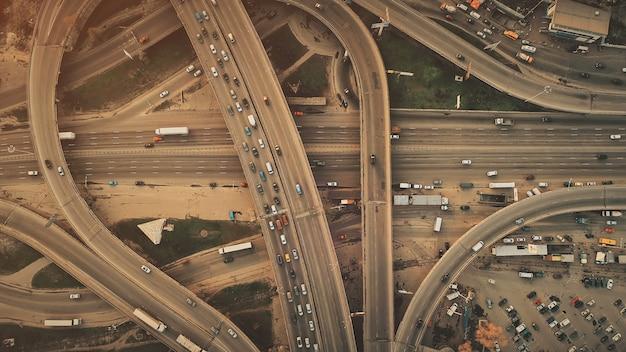 Vista aerea superiore del sistema di traffico automobilistico epic city highway. incrocio stradale trafficato percorso stradale panoramica del movimento del veicolo. business district transport development travel concept. colpo di volo del drone