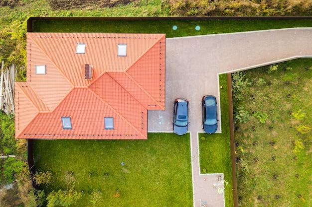 Vista aerea dall'alto del tetto in scandole di casa con finestre a soffitta e auto su cortile lastricato con prato verde.