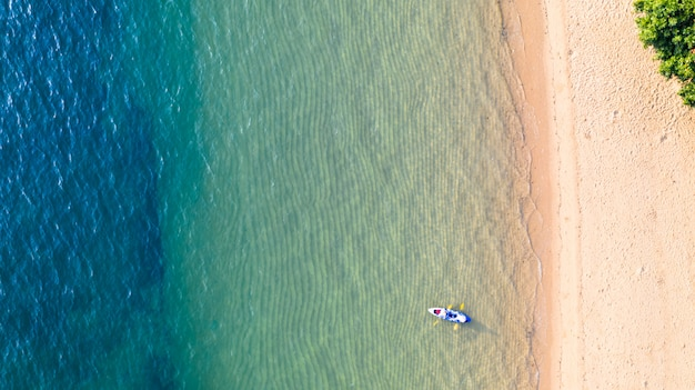 Vista superiore aerea di kayak intorno al mare con l'acqua blu smeraldo dell'ombra e fondo della schiuma dell'onda