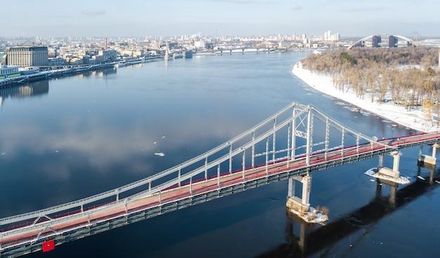 Vista aerea superiore del ponte del parco pedonale in inverno e fiume dnieper dall'alto, paesaggio urbano di kiev neve, skyline della città di kiev, ucraina