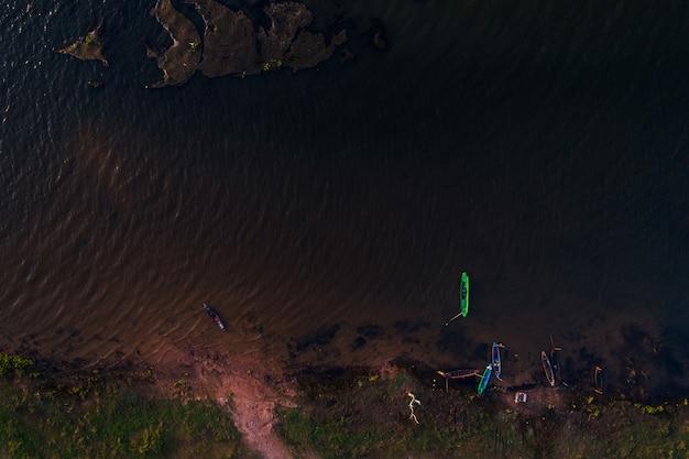 Fondo aereo del pescatore della barca e del fiume di vista superiore.
